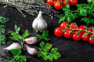 Frische Kräuter wie Thymian, Dill und Petersilie, auf einem schwarzen Hintergrund, mit Tomatenstränge und Knoblauchzehen