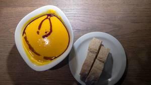 Frische Kürbissuppe Vapiano mit zwei Scheiben Ciabatta-Brot auf Holzunterlage - Nahaufnahme in Draufsicht