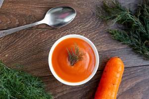 Frische Möhre und Karottensuppe mit Kräutern und einem Löffel auf einem rustikalem Holztisch
