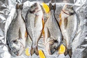 Frische, rohe Dorado-Fische mit Zitronenscheiben auf Alufolie, aus der Sicht von oben