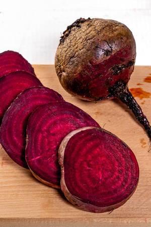 Frische rohe rote Rüben auf dem Küchenbrett