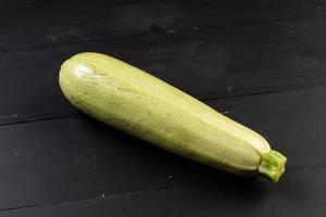 Frische rohe Zucchini auf der schwarzen Tabelle