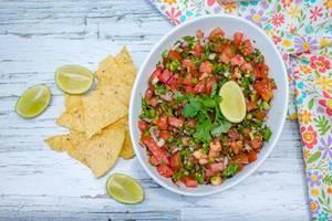 Frische Salsa in einer weißen Schale, neben Nachos und Limetten auf einem weißen Holztisch