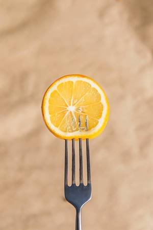 Frische Zitronenscheibe auf einer Gabel aufgespießt, vor braunem Hintergrund aus Backpapier