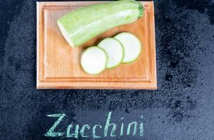 Frische Zucchini auf einem Küchenbrett mit Zucchini Schriftzug