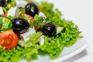 Frischer Diätsalat mit Oliven, Tomaten, Fetakäse und Gurke vor weißem Hintergrund