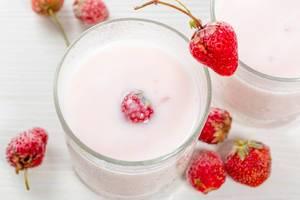 Frischer Erdbeerjoghurt mit reifen Erdbeeren auf einem weißen Tisch