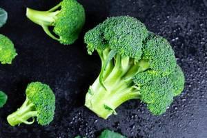 Frischer grüner Broccoli auf schwarzem Hintergrund mit Wassertropfen