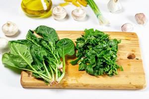 Frischer, grüner Spinatbund und geschnittene Spinatblätter auf einem Holzbrettchen