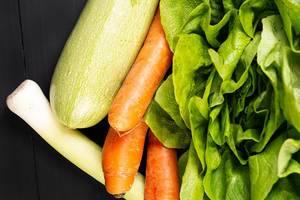 Frischer Karotten-Zucchini-Kopfsalat und Porree auf dem Tisch