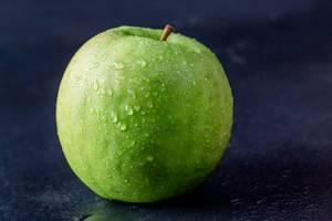 Frischer knackiger Apfel für gesunde Ernährung vor dunklem Hintergrund