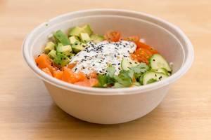 Frischer Lachs mit Avocado und Gemüse wie Gurken und Tomaten in Schüssel auf Holztisch