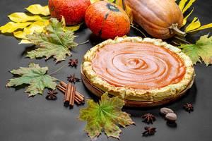 Frischer, leckerer und hausgemachter Kürbiskuchen mit Gewürzen, Kürbissen und Herbstblättern auf einem schwarzen Tisch