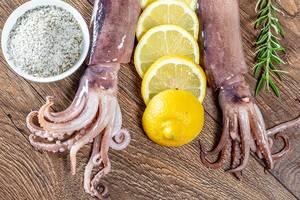 Frischer Oktopus liegt zur Zubereitung, mit Zitronen, Rosmarin und Meersalz, auf einem Holztisch