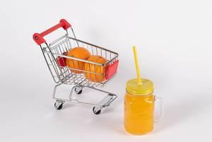 Frischer Orangensaft und Orangen in Einkaufswagen stehen für den Kauf von gesunden Nahrungsmitteln
