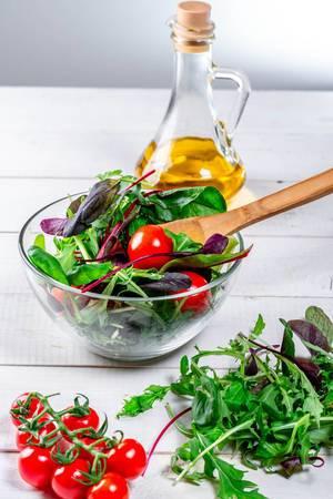 Frischer Salat mit Arugula verlässt Spinat Tomaten und Olivenöl auf einem weißen Holztisch