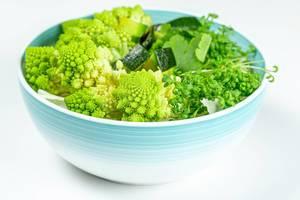 Frischer Salat mit Romanesco Kohl, Avocado, Petersilie und Wasserkresse als gesundes Diät Essen in einer Schale vor weißem Hintergrund