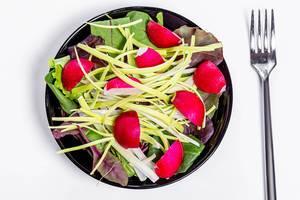 Frischer Salat mit Spinatblättern, Lauch und Radieschen auf einem schwarzen Teller in obene Aufnahme