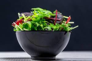 Frischer Salatmix mit Kopfsalat und Ruccola in einer schwarzen Schüssel