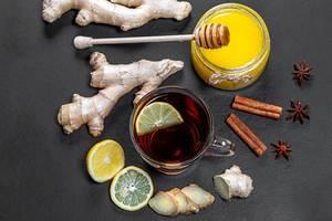 Frischer Tee mit Zitronen, Ingwer, Honig, Zimt und Anis auf schwarzem Hintergrund