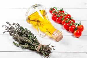 Frischer Thymian der Kirschtomaten verzweigen sich mit Olivenöl auf weißem hölzernem Hintergrund