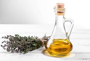 Frischer Thymian mit Olivenöl auf weißem Holztisch