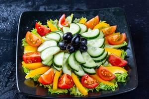 Frischer, vitaminreicher Salat mit Gurke, Paprika, Oliven und Tomaten auf schwarzem Teller