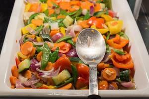 Frisches Gemüse als gesunde Beilage zum Mittagessen, in einem weißen Behälter am Essensbüfett