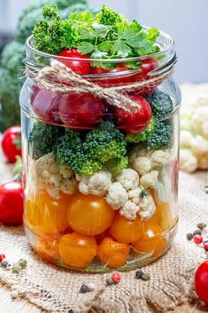 Frisches Gemüse in einem Einlegeglas auf einem Leinentuch