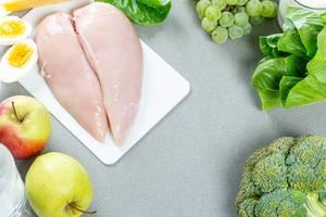 Frisches Hähnchenfleisch-Filet, grüne Äpfel und Weintrauben, Salat und Brokkoli auf grauem Hintergrund, aus der Sicht von oben