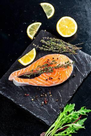 Frisches Lachssteack mit Thymian-Kräutern, Zitronenscheiben und Salatblätter auf einem schwarzen Schiefersteinteller