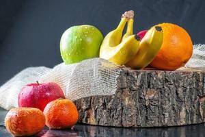 Frisches Obst mit Wasserspritzern auf einem Baumstamm und Sackleinen