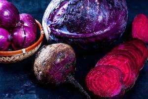 Frisches purpurrotes Gemüse auf dunklem Hintergrund