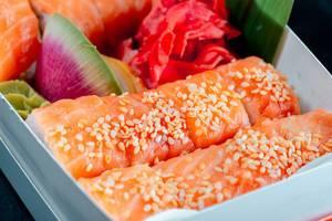 Frisches Sushi in einer Box mit Sesam, eingelegtem Ingwer und Wasabi in einer Box