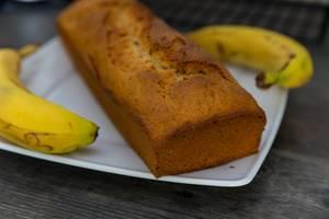 Frischgebackenes Bananenbrot, mit knuspriger Kruste, auf einem weißen Teller, neben zwei Bananen
