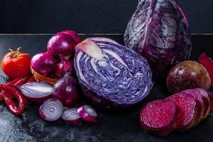 Frishes Gemüse, rote Zwiebeln, Rotkohl, rote Beete, Chili und Tomaten mit Wassertropfen auf schwarzem Untergrund