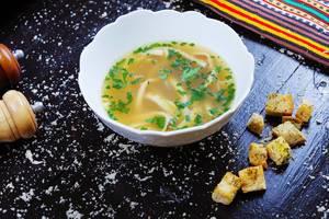 Frittatensuppe in einem weißen Tiefteller und Croutons auf einem schwarzen Tisch