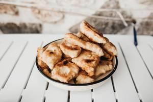 Frittierte Brötchen auf dem Teller. Frühstück auf balkanische Art