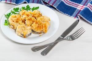 Frittierte Fischstücke mit frischen Zwiebeln und Petersilie,  auf einem weißen Teller