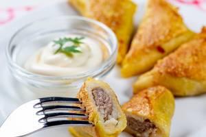 Frittierte Pfannkuchen mit Hackfleischfüllung und weißer Sauce