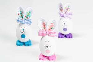Frohe Ostern: drei Osterhasen aus Eiern gebastelt vor weißem Hintergrund