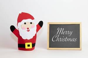 Frohe Weihnachten auf einer Schiefertafel mit einem Weihnachtsmann