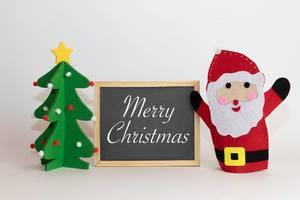 Frohe Weihnachten geschrieben auf einer Tafel mit einem Weihnachtsbaum und Weihnachtmann