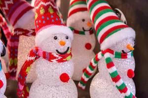 Fröhliche Kunst Schneemänner mit bunten Mützen und Schals