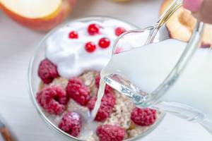 From a glass jug pour milk into oatmeal with fruit (Flip 2019)