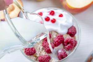 From a glass jug pour milk into oatmeal with fruit