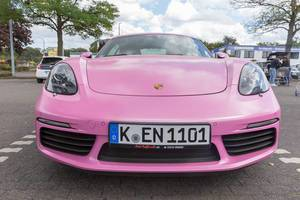 Front view of a Porsche 718 Cayman sports car in pink, at a German parking lot