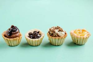 Front view of mini cake tarts. Desserts. Blue background