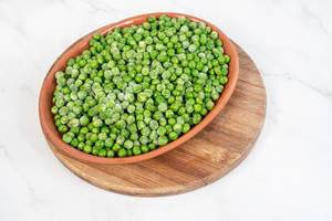 Frozen Green Peas in the bowl above white background (Flip 2019)