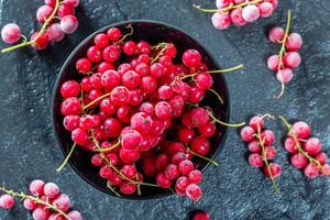 Frozen red currant in a black bowl on a black stone tray. Top view